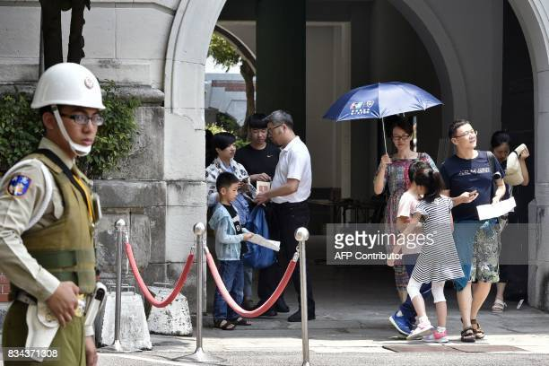 A military policeman keeps watch at an exit for public visitors to the Presidential Palace complex in Taipei on August 18 2017 A samurai...