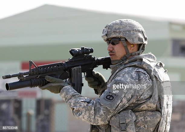A US military policeman stands guard after a US armoured personnel carrier was hit by a roadside bomb in the Iraqi city of Mosul some 370 kms north...