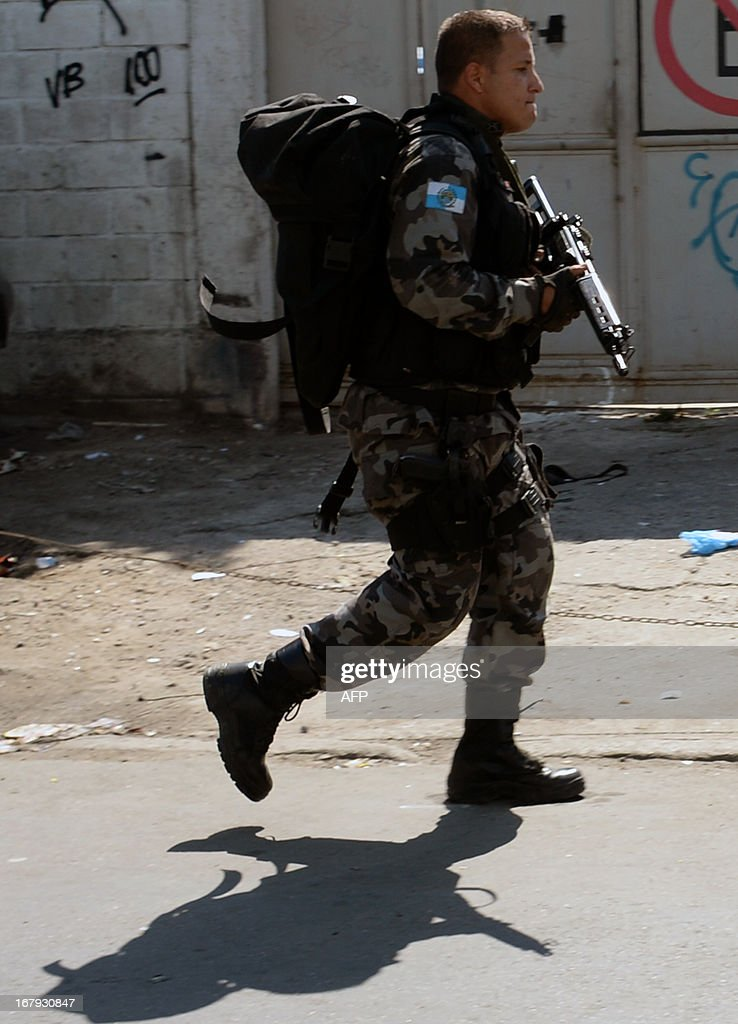 A Military policeman takes part in an operation against drug dealers at Mare del Rio shantytown in Rio de Janeiro on May 2, 2013. The operation is part of a government strategy designed to combat crime and reassert full control of the Rio de Janeiro metropolis ahead of the upcoming FIFA Confederations Cup, the football World Cup of 2014 and the Olympic Games two years later.