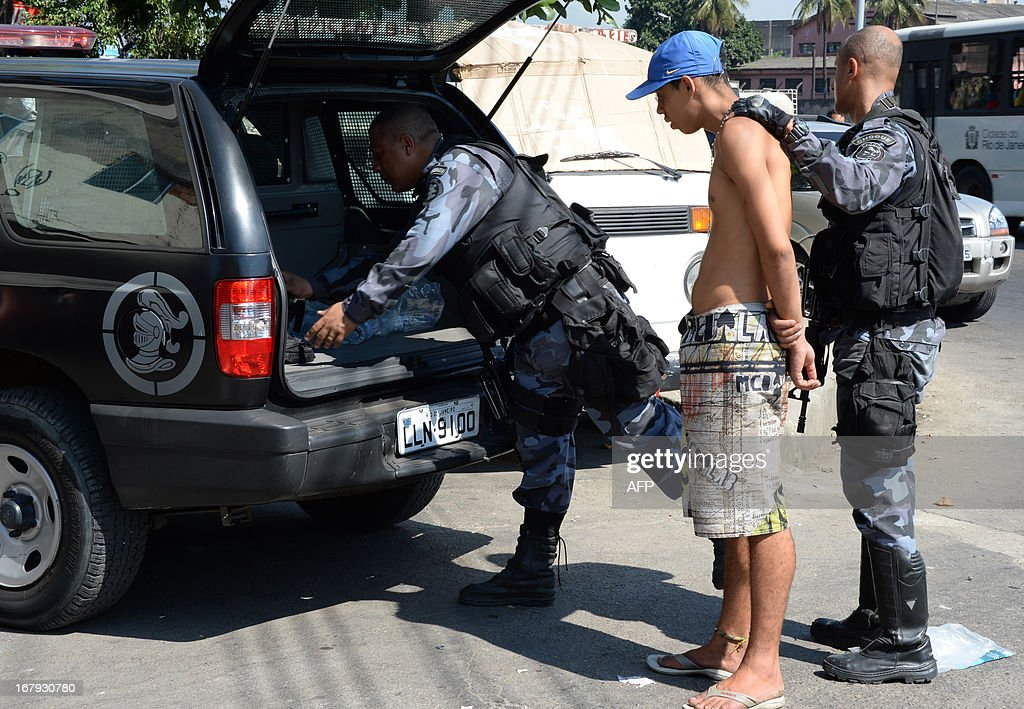 Military policemen arrest an alleged drug dealer as they carry out an operation at Mare del Rio shantytown in Rio de Janeiro on May 2, 2013. The operation is part of a government strategy designed to combat crime and reassert full control of the Rio de Janeiro metropolis ahead of the upcoming FIFA Confederations Cup, the football World Cup of 2014 and the Olympic Games two years later.