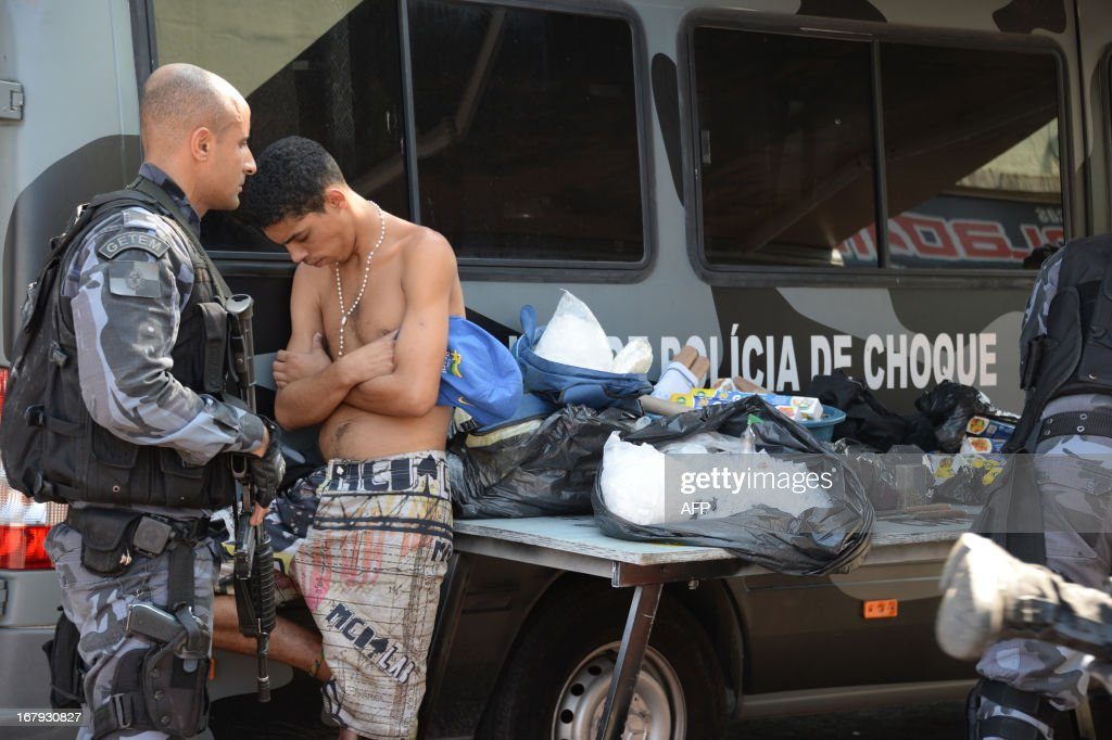 Military policemen arrest an alleged drug dealer as they carry out an operation at Mare del Rio shantytown in Rio de Janeiro on May 2, 2013. The operation is part of a government strategy designed to combat crime and reassert full control of the Rio de Janeiro metropolis ahead of the upcoming FIFA Confederations Cup, the football World Cup of 2014 and the Olympic Games two years later. AFP PHOTO /VANDERLEI ALMEIDA