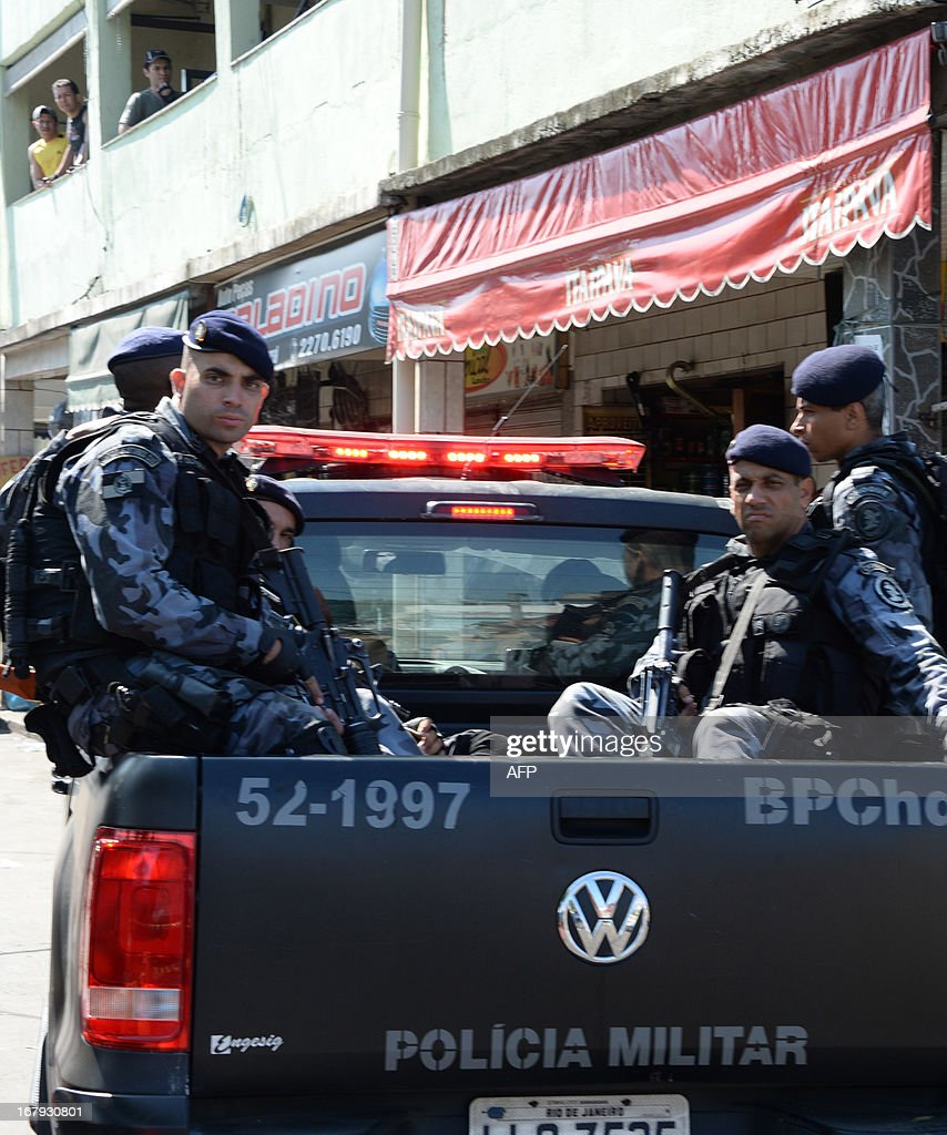 Military policemen carry out an operation against drug dealers at Mare del Rio shantytown in Rio de Janeiro on May 2, 2013. The operation is part of a government strategy designed to combat crime and reassert full control of the Rio de Janeiro metropolis ahead of the upcoming FIFA Confederations Cup, the football World Cup of 2014 and the Olympic Games two years later. AFP PHOTO /VANDERLEI ALMEIDA
