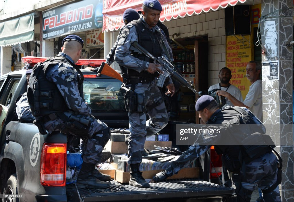 Military policemen carry pirate compact disks and drugs after arresting alleged drug dealers as they carry out an operation at Mare del Rio shantytown in Rio de Janeiro on May 2, 2013. The operation is part of a government strategy designed to combat crime and reassert full control of the Rio de Janeiro metropolis ahead of the upcoming FIFA Confederations Cup, the football World Cup of 2014 and the Olympic Games two years later. AFP PHOTO /VANDERLEI ALMEIDA
