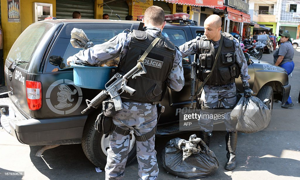 Military policemen check bags after arresting alleged drug dealers as they carry out an operation at Mare del Rio shantytown in Rio de Janeiro on May 2, 2013. The operation is part of a government strategy designed to combat crime and reassert full control of the Rio de Janeiro metropolis ahead of the upcoming FIFA Confederations Cup, the football World Cup of 2014 and the Olympic Games two years later.