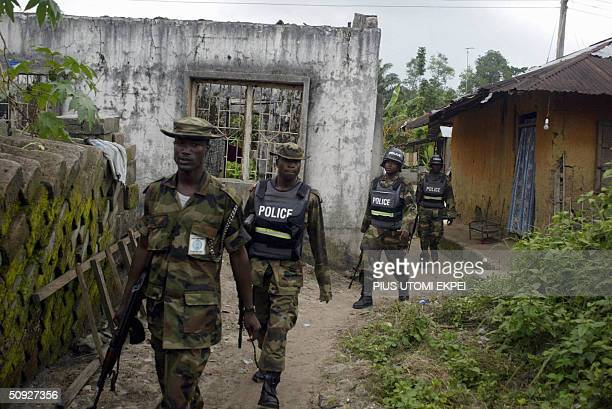 Military policemen walk past a building burnt by ethnic militias in search of arms and criminals at Omadino village in Warri South district of Niger...