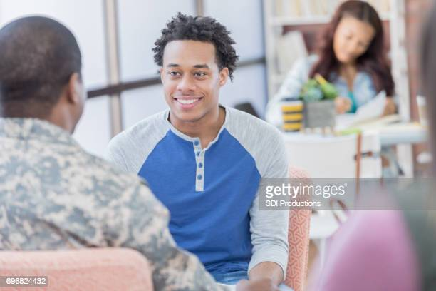 Military recruitment officer visits with interested young man