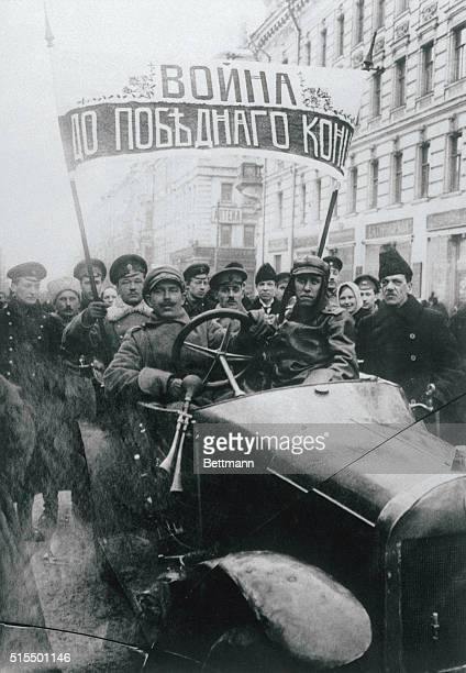 Military revolutionaries in Russia parade down a street in a car with a banner