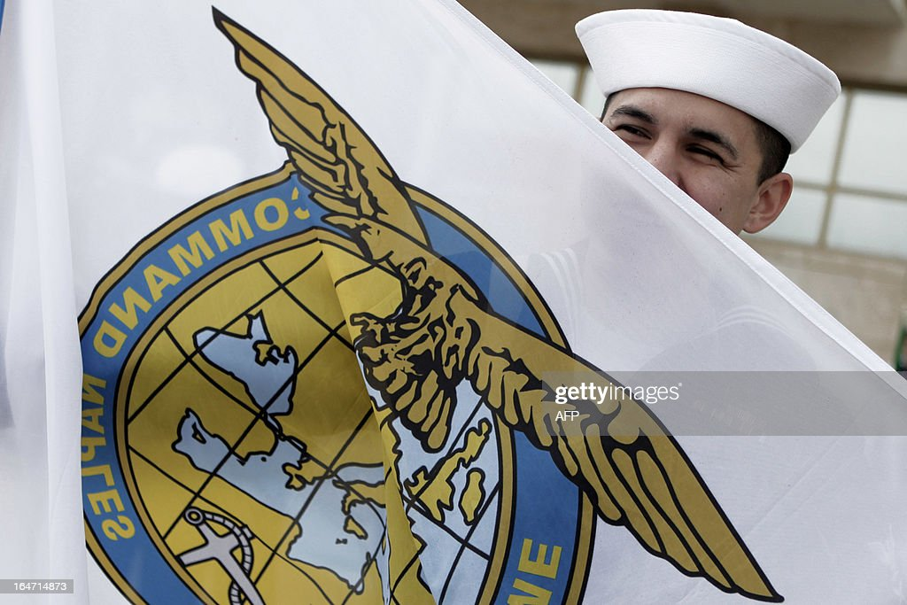 U.S. Military sailorman holds a flag of Allied Maritime Command Naples during the deactivation ceremony of Navsouth Base Headquarter in Nisida Island near Naples on March 27, 2013. The new NAVSOUTH headquarter will be based at Northwood in United Kingdom. AFP PHOTO/CONTROLUCE