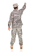 rear view of military serviceman pointing empty space