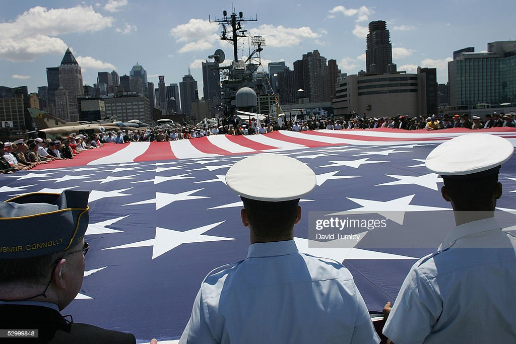 U.S. military servicemen unfurl an enormous U.S. flag while aboard the USS Intrepid during a Memorial Day service May 30, 2005 in New York City. Memorial Day commemorates members of the armed forces who died serving their country.