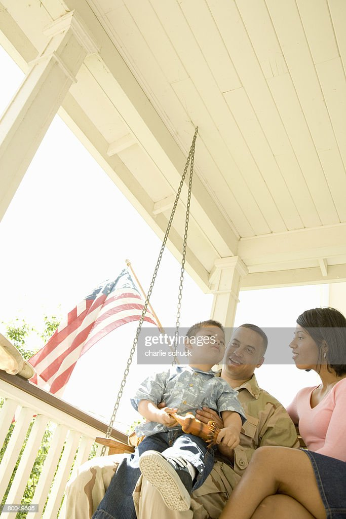 Military solder and family sitting on porch swing