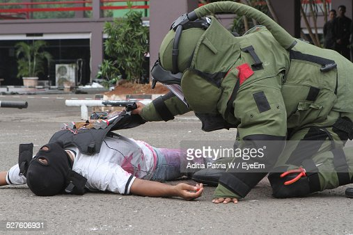 Military Soldier Defusing Bomb On Criminal Body On Street