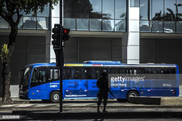 A military soldier stands guard as a bus passes in Rio de Janeiro Brazil on Saturday July 29 2017 Thousands of military soldiers had been activated...