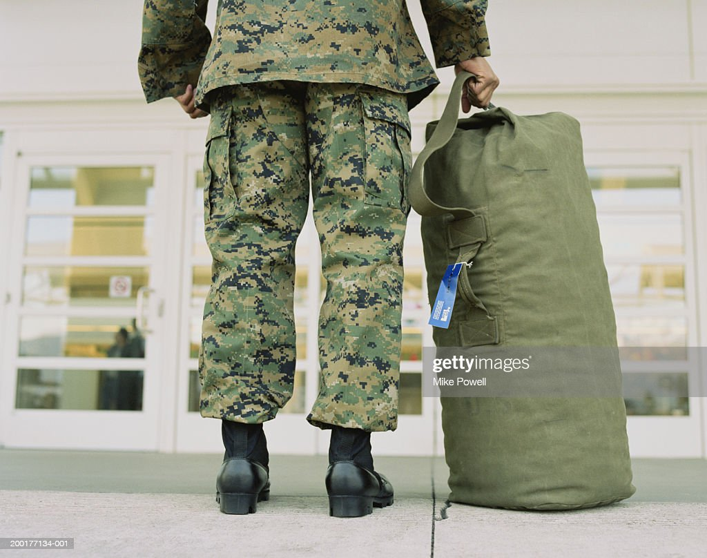Military soldier with bag in airport, low section