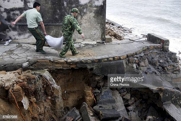 Military soldiers carry earthbags to reinforce a bank collapsed by billow in coastal Daao Village of Pinghai Township as Typhoon Chanchu approaches...
