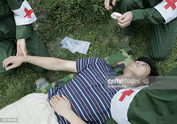 Military soldiers give first aid to a simulated heatstroke patient during a drill to deal with emergencies in scorching heat on July 4 2005 in...