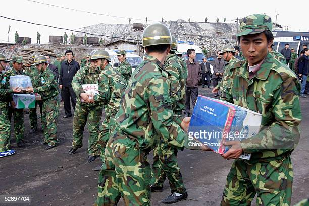 Military soldiers remove relief goods at a coal mine accident site on April 25 2005 in Jiaohe County of Jilin Province northeast China A flooding has...