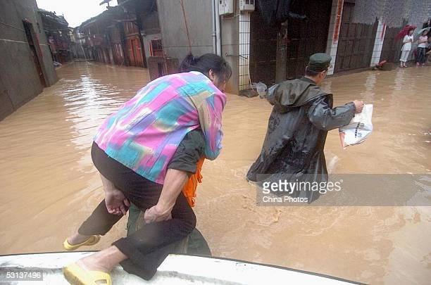 Military soldiers rescue a woman trapped by flood on June 22 2005 in Shunchang County of Fujian Province southeast China According to the State...