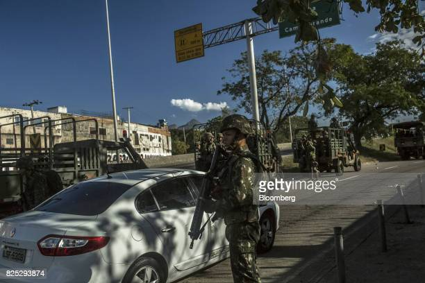 Military soldiers stand guard along the Red Line highway in Rio de Janeiro Brazil on Sunday July 30 2017 Thousands of military soldiers had been...
