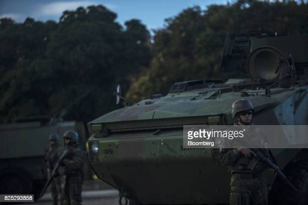 Military soldiers stand guard next to an armored vehicle in Rio de Janeiro Brazil on Saturday July 29 2017 Thousands of military soldiers had been...