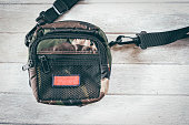 'Military style' shoulder bag on white wooden background. Top view