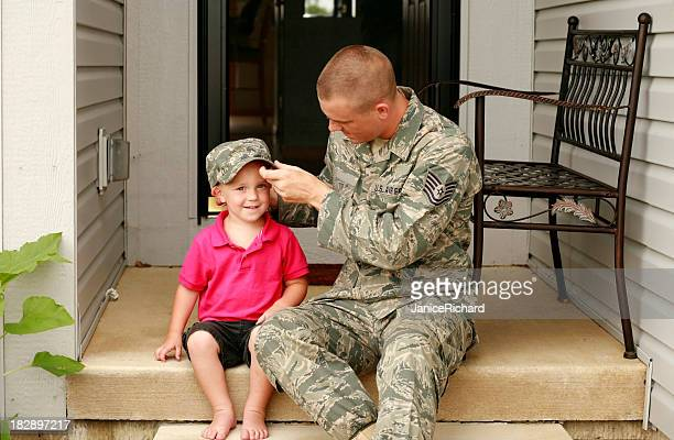 A military styled father letting his son try on his hat