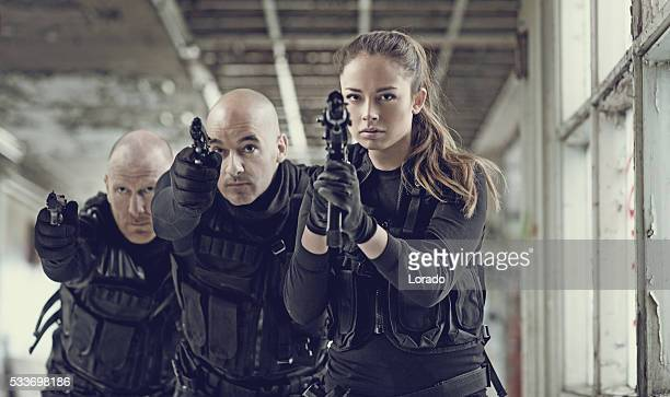 Military swat team members during incursion in abandoned warehouse