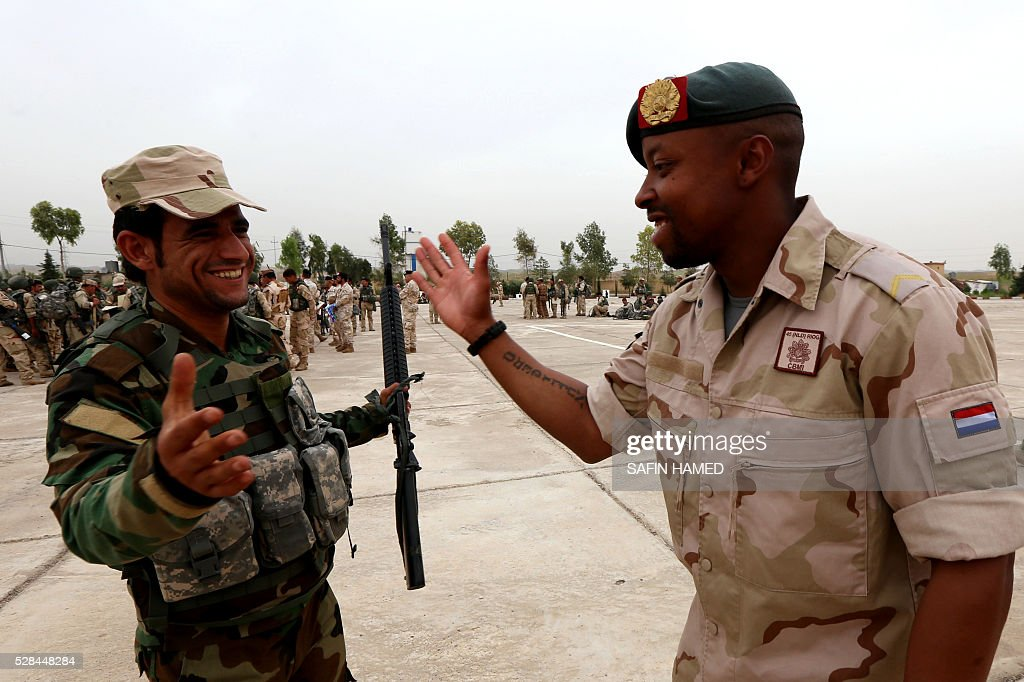 A military trainer from the Netherlands (R) greets a Kurdish Peshmerga fighter during a graduation ceremony on May 5, 2016 at the Kurdistan Training Coordination Center (KTTC) of Arbil, the capital of the autonomous Kurdish region of northern Iraq. The KTTC is a joint effort of the Dutch, Italian, British and German governments which aims to unify the military assistance of these countries. / AFP / SAFIN