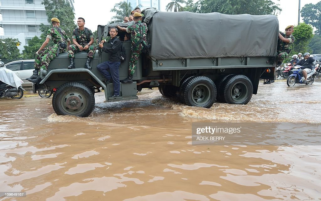 A military truck is used to help employee reaching their offices at the flooded main street in Jakarta on February 18, 2013. Floods which have made more than 19,000 people homeless and killed three brought parts of the Indonesian capital to a standstill on January 17, with even the president forced to roll up his trousers.