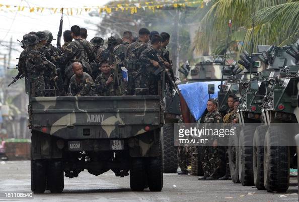 A military truck loaded with soldiers speed past armored personnel carrier near the site of a standoff as firefighting between government troops and...