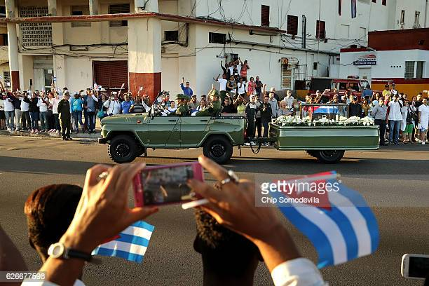 A military truck pulls a trailer with the flagdraped chest that holds the remains of former President Fidel Castro as thousands of Cubans line the...
