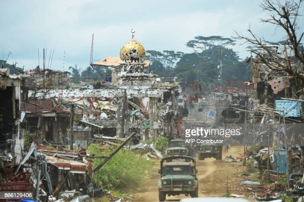 Military trucks drive past destroyed buildings and a mosque in what was the main battle area in Marawi on the southern island of Mindanao on October...
