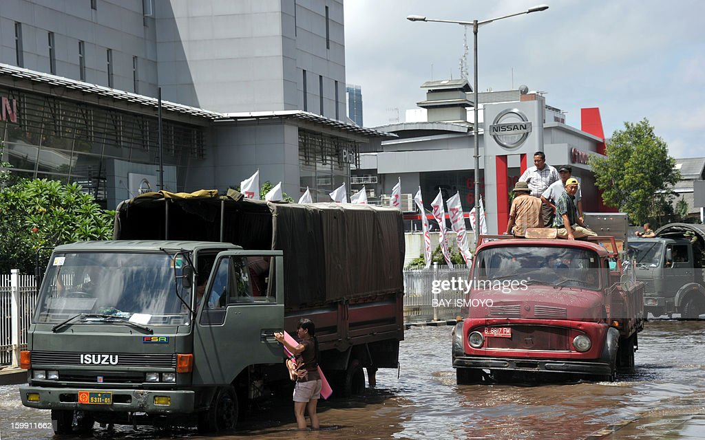Military trucks drive through a flooded road to distribute relief goods in Jakarta on January 23, 2013 as some areas of the capital remains submerge by flood water. A spokesman for Indonesian National Disaster Mitigation Agency (BNPB) said more than 30,000 people were still living as evacuees on January 22, while 20 people were killed during the widespread flooding that hit Jakarta that has been going on for a week. AFP PHOTO / Bay ISMOYO