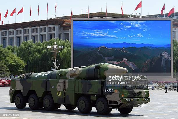 A military vehicle carries DF21D missile past a display screen featuring an image of the Great Wall of China at Tiananmen Square in Beijing on...