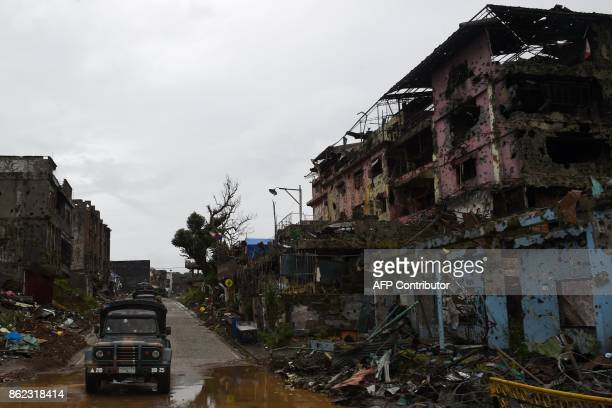 A military vehicle passes bombedout buildings inside the battle area of Bangolo district in Marawi on October 17 2017 Philippine President Rodrigo...