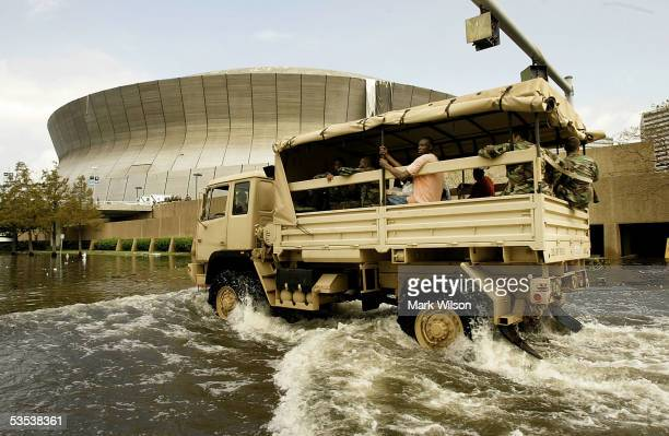 A military vehicle takes people to the Superdome as water begins to rise in the area August 30 2005 in New Orleans Louisiana Thousands of people are...