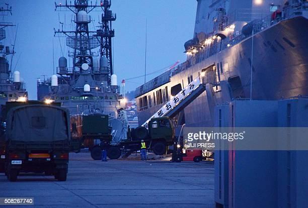 Military vehicles carry groundbased ballistic missile interceptors into Japan's Maritime SelfDefense Force transport vessel Oosumi at the MSDF base...