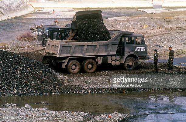 Military vehicles of the Italian corps of engineers of Stabilisation Force a NATOled multinational peacekeeping force on the bed of the Drina River...