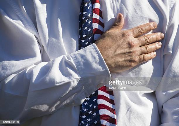 A US military veteran places his hand over his heart during the Pledge of Allegiance during a Veterans Day ceremony at the Vietnam Veterans Memorial...