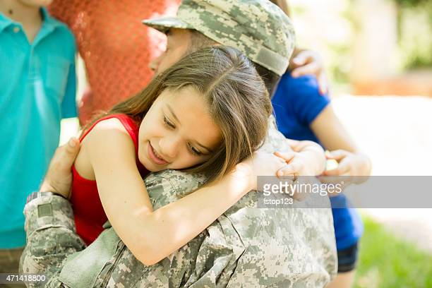 U.S. military veteran welcomed home by family. Children, hugs.