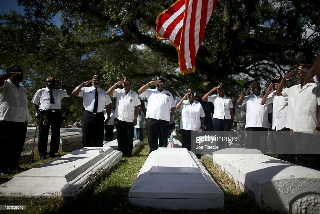 Military veterans salute during a Veterans Day ceremony held in the Grove Bahamian Cemetery on November 11, 2013 in Coconut Grove, Florida. The ceremony was held by the Coconut Grove American Legion Post #182 in honor of those veterans who have served the United States.