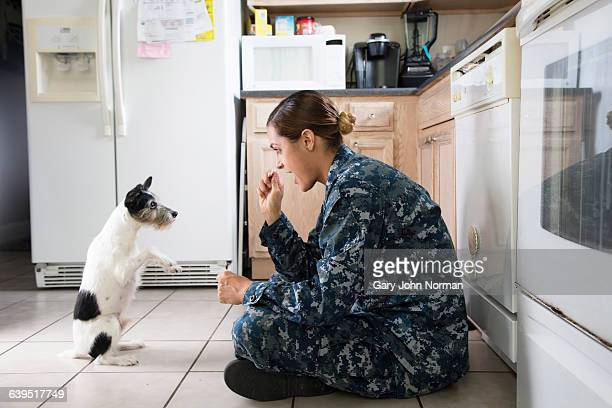 Military woman with her pet dog at home