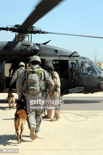 Military working dog handlers board a helicopter. : Foto stock