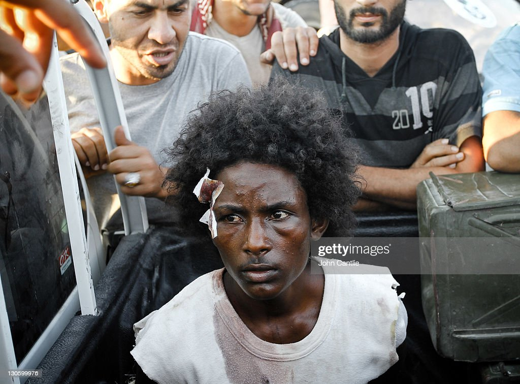 A militia fighter of Mauritanian origin and loyal to Gaddafi is captured and taunted by NTC fighters near Colonel Gaddafi's home city of Sirte on September 19, 2011 in Libya. NTC forces are continuing to advance on Colonel Muammar Gaddafi's home town of Sirte.