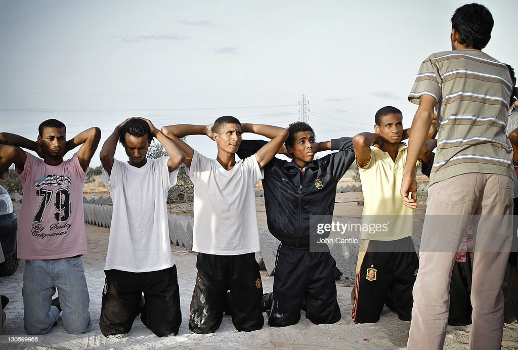 Militia fighters loyal to Gaddafi are captured and taunted by Misratan NTC fighters near Colonel Gaddafi's home city of Sirte on September 20, 2011 in Libya. NTC forces are continuing to advance on Colonel Muammar Gaddafi's home town of Sirte.