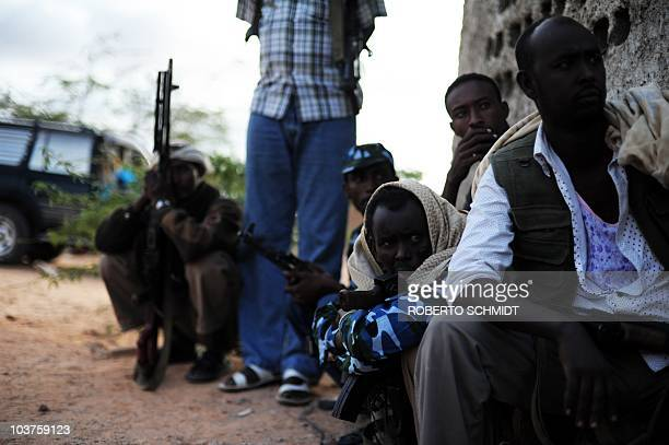 Militiamen and pirates sit in the courtyard of a lot used by a Galmadug administration official as a temporary refuge in the town of Wisil on August...