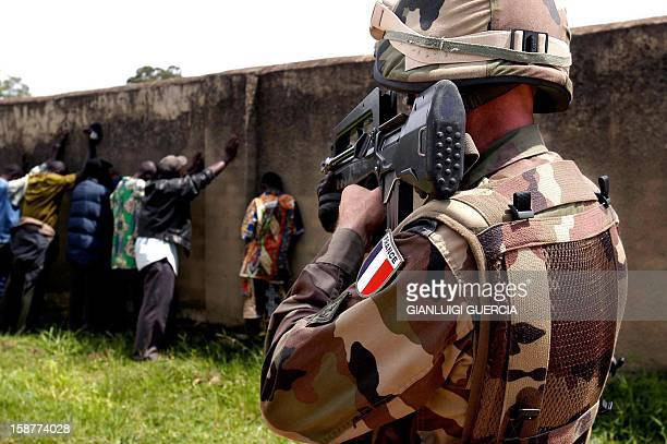 Militiamen are lined up against a wall and watched at gunpoint by a French soldier 26 June 2003 after a French Army patrol confiscated them some HK47...