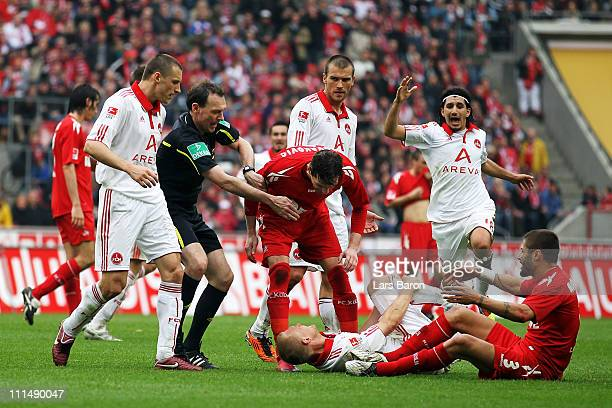 Milivoje Novakovic and Youssef Mohamad of Koeln argue with Andreas Wolf of Nuernberg next to referee Florian Meyer during the Bundesliga match...