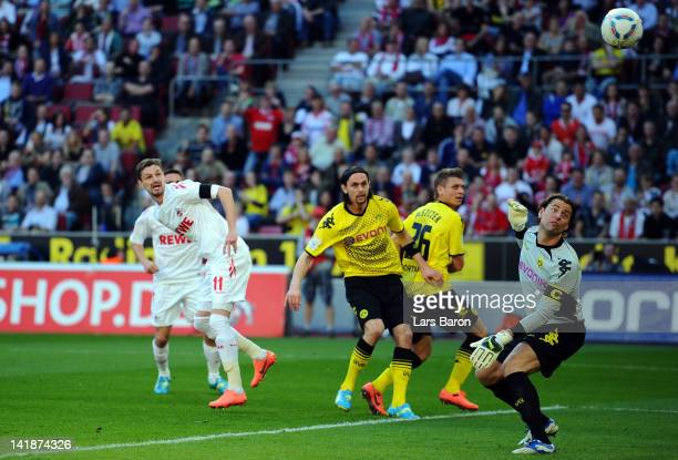 Milivoje Novakovic of Koeln heads his teams first goal over goalkeeper Roman Weidenfeller of Dortmund during the Bundesliga match between 1 FC Koeln...