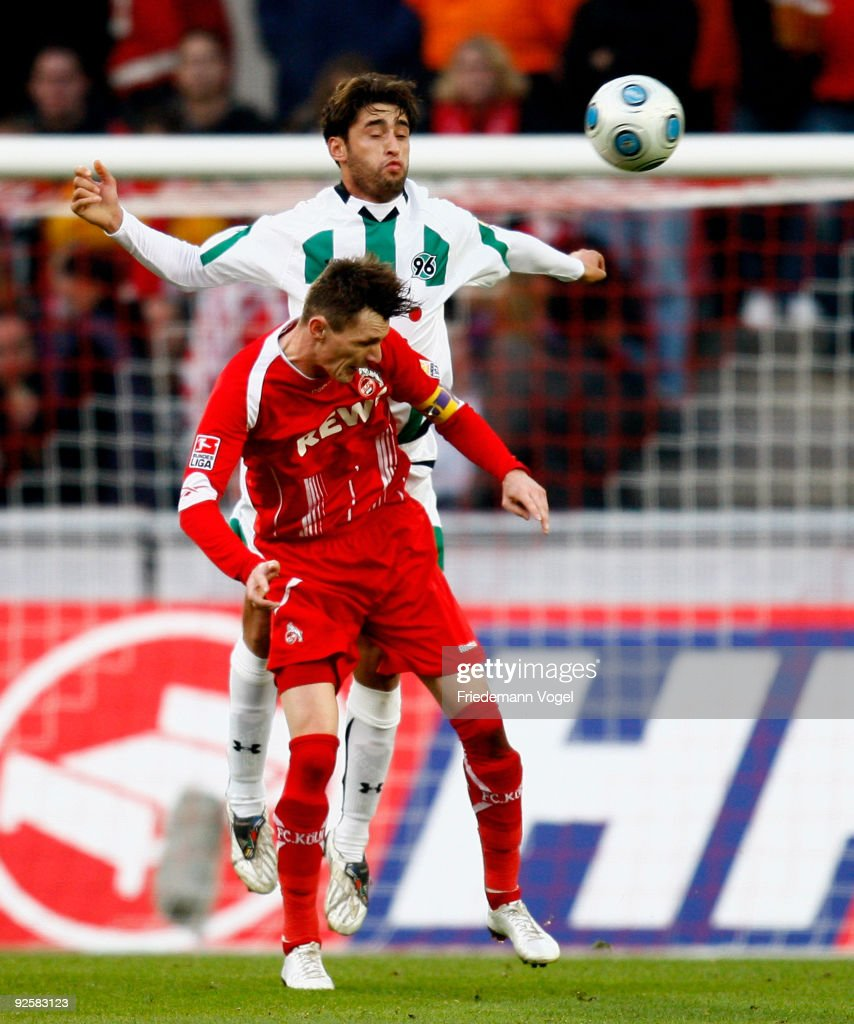 Milivoje Novakovic of Koeln in action with Karim Haggui of Hannover during the Bundesliga match between 1 FC Koeln and Hannover 96 at the Rhein...